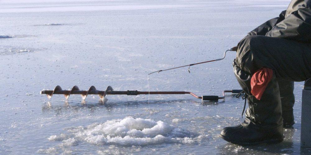 Рыболов на льду ловит рыбу